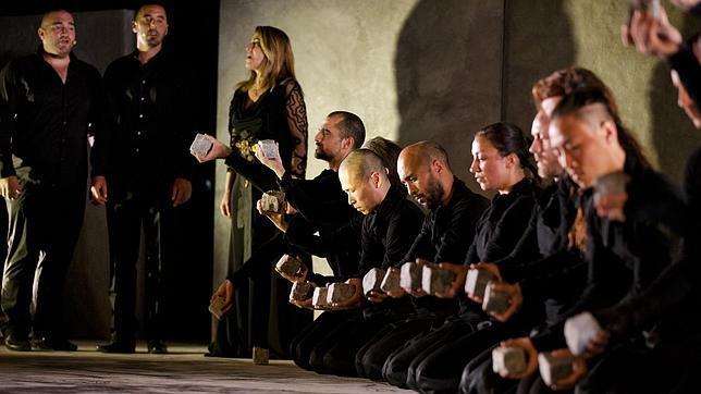 Imagen de los músicos y bailarines de PUZ/ZLE arrodillados sujetando el elemento central de la obra: la piedra. Fotografía de J.L. Fernández.