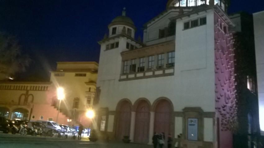 Mercat de les Flors y su cúpula iluminada con el fresco de Miquel Barceló desde el Institut del Teatre. Se puede ver la Plaça Margarida Xirgu, donde se habilita el aparcamiento gratuito, y al fondo el Teatre Lliure.